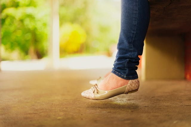 A woman's legs she is wearing the wardrobe essential a pair of flats shoes.