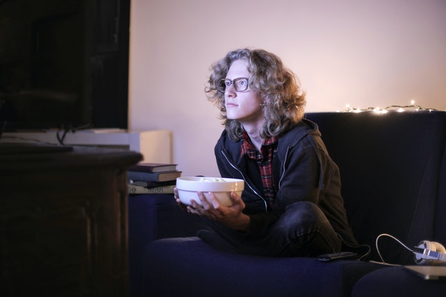 A boy with a bowl of popcorn leaning forward as he watches a movie as it is better than reading a book.