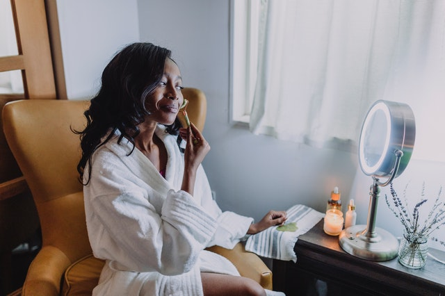 A woman in a robe sitting in front of a mirror using a roller and investing in herself in 2021.