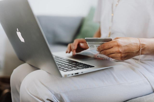 A woman with a laptop and a credit card purchasing exclusive products online.