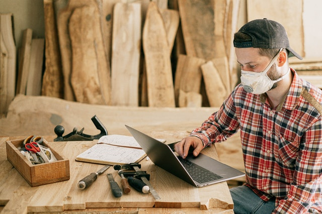 A man with a laptop at a woodwork desk buying respirator face mask online and wearing one.