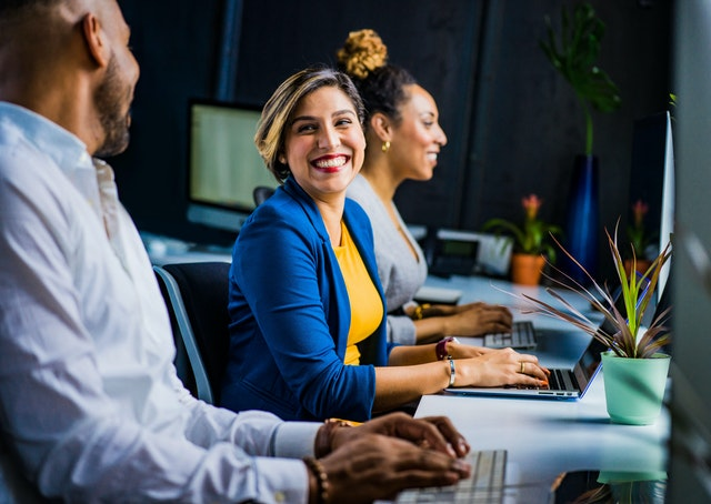 A woman smiling at her colleagues as they sit at their desks using their laptops to design a good website and improve their brand image.