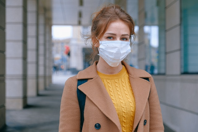 A woman standing on the street wearing a respirator face mask from an online store.