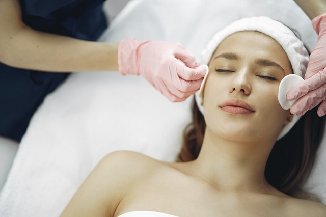 A woman lying with her eyes closed as a beautician transforms her look this year by giving her a facial treatment.