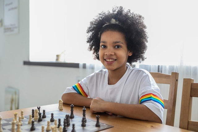 A young girl smiling as she sits with her own chess set and plays with it.