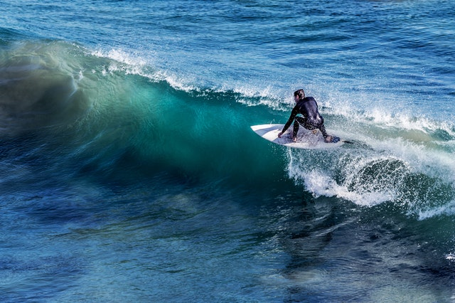 A man on a surfboard riding a wave during surfing lessons this year.