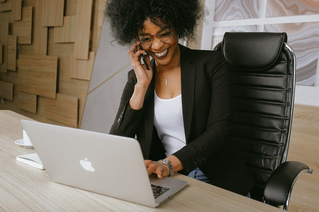 A business woman at a desk using a laptop and talking on the phone using a virtual phone system with benefits.