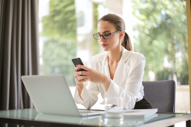 A business woman at a desk with a laptop and texting using a virtual phone system.