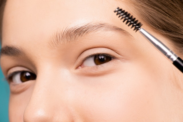 A woman using a brush to get dream brows by colouring them.