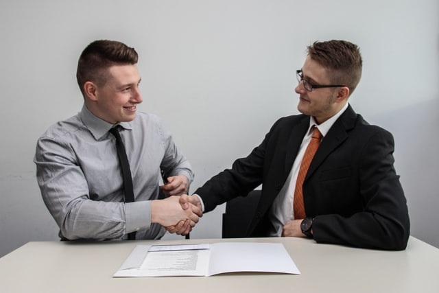 Two men shaking hands as they have been hired for a business that was previously struggling with staff.