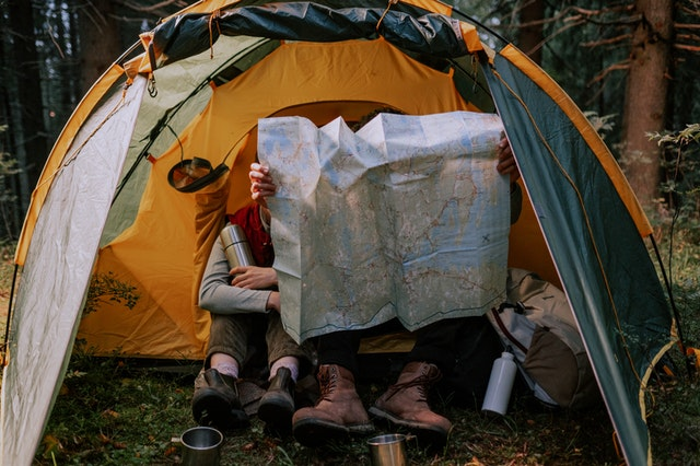 A couple reading a map in a tent that they hired to see Australia.